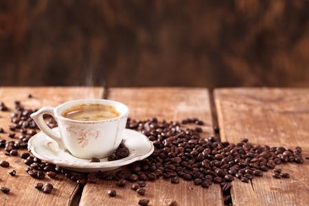Tazza di caffè e chicchi di caffè sul tavolo di legno.