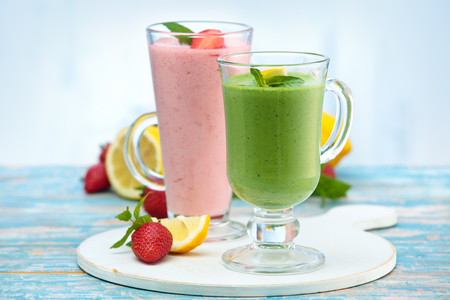 Banana, spinach and strawberry smoothie with mint leaves on wooden rustic table.