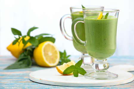 Spinach smoothie with mint leaves and lemon on table.