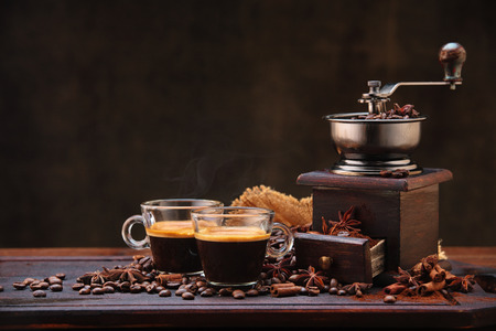 molinillo: Coffee beans and grinder on wooden table  with cinnamon and anise stars.