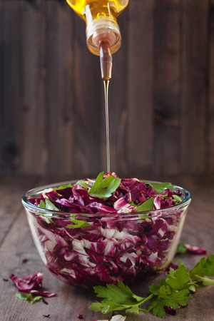 Shredded red cabbage in glass bowl with parsley and oil. Stock Photo