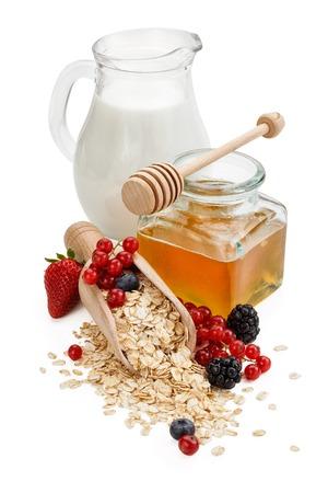 Oats, honey and fresh fruits isolated on white background.