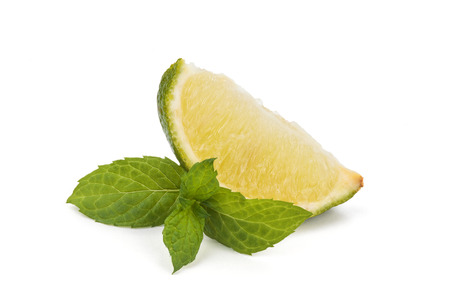 Close up shot of sliced lime and mint leaves. Isolated on a white background