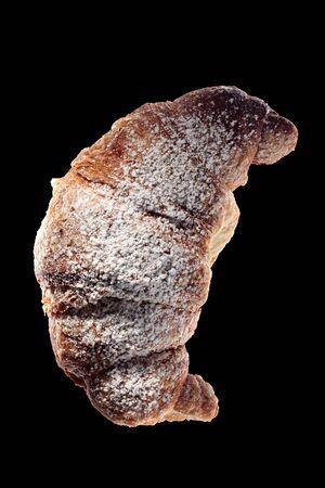 Shot of fresh croissant isolated on black background.