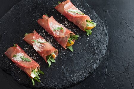 Prosciutto rolls stuffed with arugula and pears on black slate. Stock Photo