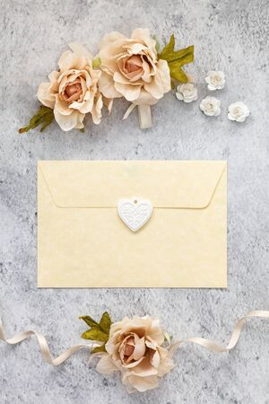 Wedding invitation card  paper laying on table decorated with roses.
