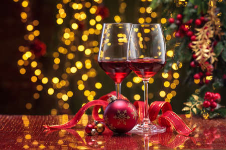 Red wine in wineglasses and Christmas ball against holiday lights background. Imagens