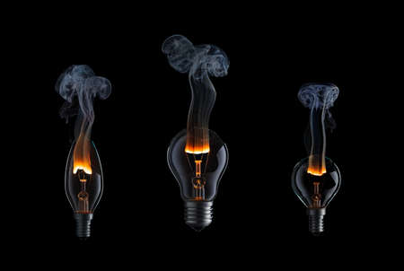 Collection of light bulbs with fire and smoke on black background.