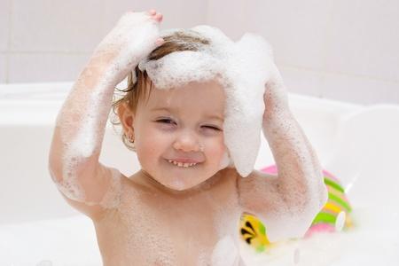 champu: lindo bebé está lavando el pelo en el baño Foto de archivo