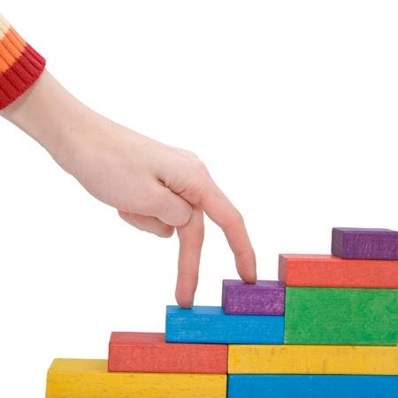 subiendo escaleras: Piso de arriba Mujer escalada mano que está hecha de bloques de juguete de madera. Aislado sobre fondo blanco