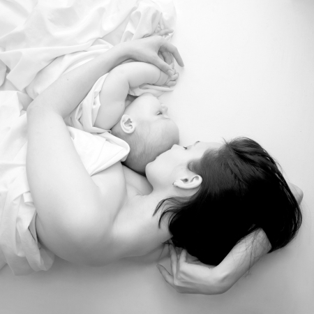 pacification: Black and white portrait - a young mother and her baby sleeping in bed  The symbol of maternal love, care, happiness and pacification