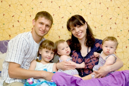 Happy smiling young family, five people - mother, father,\ elder daughter and two twins baby girls The family is sitting at\ home on the sofa