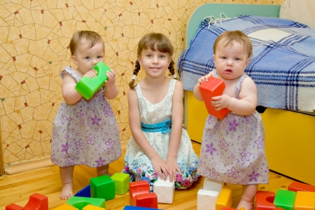 Three sisters - a  preschooler girl and two twins baby toy building of the blocks  Older sister teaching younger  Stock Photo - 13888905