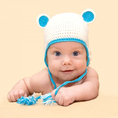 Portrait of lovely smiling newborn baby with blue eyes, wearing a white and blue knitted cap with ears closeup  Isolated on a beige background  photo