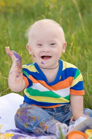 disable: Little baby boy with Down syndrome painting finger paints on white paper with a smile  Happiness is in creativity
