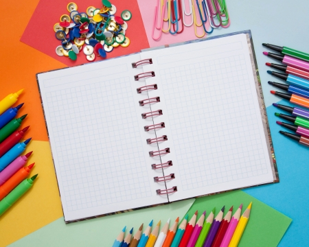 School, office, or artistic accessories - open notebook, colored paper, colored pencils, markers, paper clips, buttons  Ready for your logo, text or symbol  photo