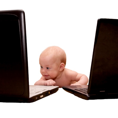 attentiveness: Baby with blue eyes working on two laptops at the same time