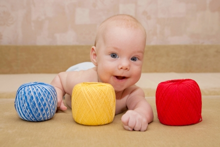 Charming baby lying on the couch with a ball of yarn for knitting photo