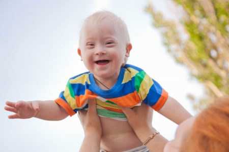 eyes looking down: Portrait of a baby with Down syndrome. A mother picking up her son, the child is happy and flying up