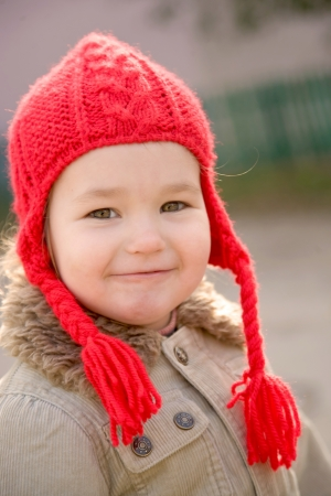Autumn portrait of a beautiful little girl wearing a red hand knitted hat with braids. Smiling face closeup photo