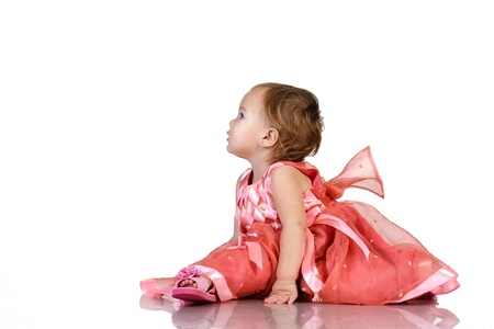 Baby in an elegant pink dress. isolated on white photo
