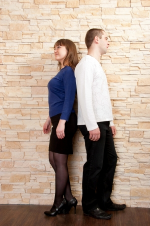 Young couple - a boy and girl standing back to back against a brick wall. Quarrel, dispute, compromise search photo