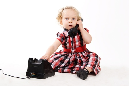 calling on phone: little curly-haired blonde girl, wearing a checkered dress, talking on the old black phone, calling mom isolated on white  Retro style