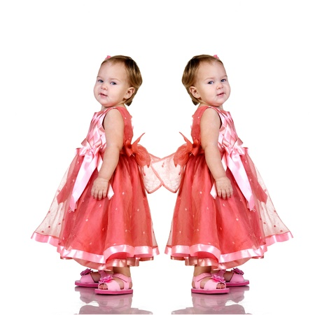 twin sister: Identical twin baby girls  in an elegant pink dress isolated on white background.