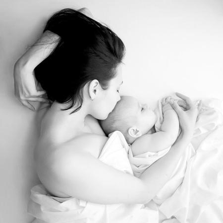 어머니의: 흑백 초상화 - 침대에서 잠을 젊은 어머니와 그녀의 아기. 어머니의 사랑, 배려, 행복과 평정의 상징