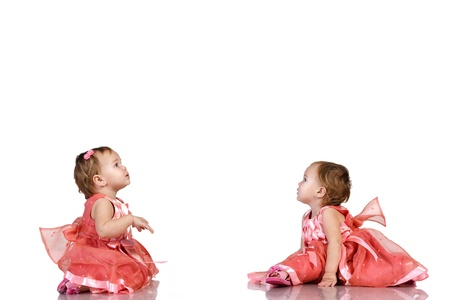 twin sister: Identical twin baby girls in an elegant pink dresses looking carefully at something in their  birthday. Place for your text or logo, isolated on white background.
