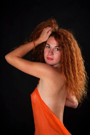 Sexy young red-haired woman on a black background photo