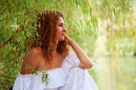 Beautiful young red-haired woman in white dress with flower in her hair or bride sitting at willow by the river, resting and dreaming Stock Photo - 15567697