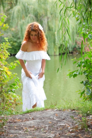 Beautiful young red-haired woman in white dress with flower in her hair or bride or undine, coming out of the river in thickets of willow Stock Photo - 15567699