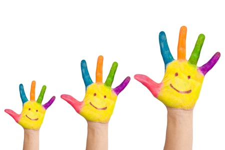 family fun: Three colorful hands with smile of family - mother, father and baby Stock Photo