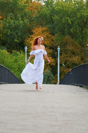 Beautiful red-haired young woman, wearing in white dress or bride running across a bridge in the autumn park Stock Photo - 15571721