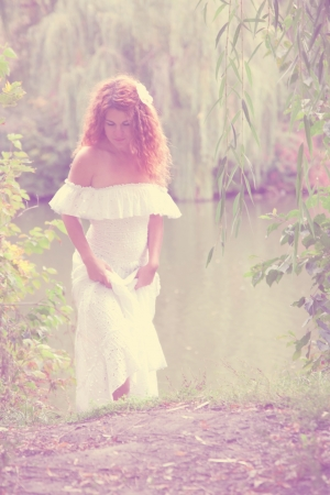 Vintage photo - beautiful young red-haired woman in white dress with flower in her hair or bride or undine, coming out of the river in thickets of willow. Retro style Stock Photo - 15596098