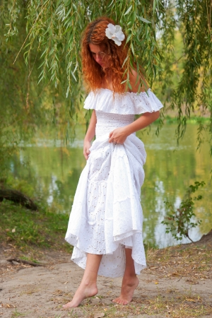 bride or undine, coming out of the river in thickets of willow photo