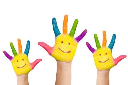 solidaridad: Pintado en diferentes colores, con las palmas pintadas caras sonrientes, un par de manos levantadas. Saludo o votar la aprobación o el trabajo en equipo. Foto de archivo