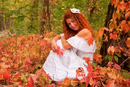 Beautiful red-haired young woman sitting among red leaves in autumn forest  photo