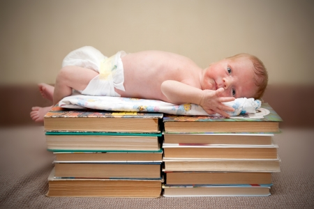 Tiny naked newborn baby lying on a pile of books photo