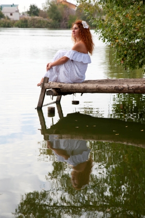 undine: Beautiful young red-haired woman in white dress with flower in her hair or bride or undine sitting on a wooden bridge on the lake