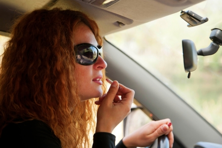 putting in: red-haired woman putting makeup on her lips looking in the mirror of car
