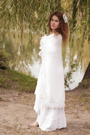Barefoot young woman in white dress and white robe, walking along the river. Retro style. photo