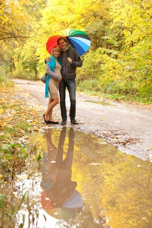 Happy pregnant woman and a man walking in the autumn forest under a rainbow colorful umbrella and reflected in a puddle photo