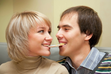 Loving young couple eating one cookie for two and looking eye to eye photo