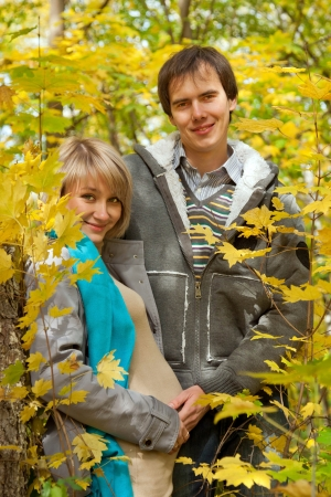 Love beautiful young pregnant couple in the autumn forest in the thickets of maple photo