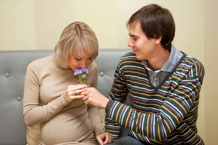 A man giving his pregnant wife a bouquet of flowers. A happy family photo