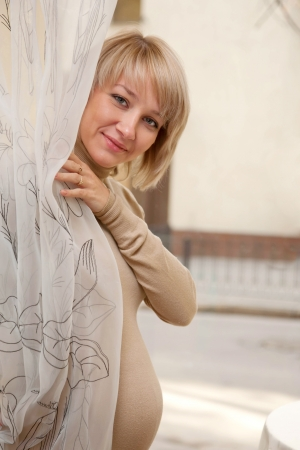 Pretty young pregnant woman looking out from behind the curtain photo