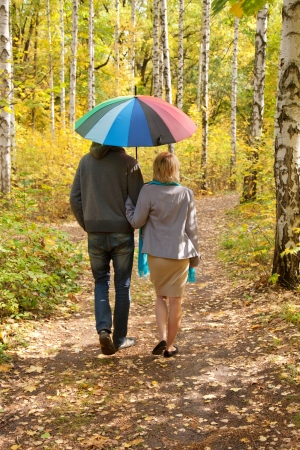Happy pregnant woman and a man walking in the autumn forest under a rainbow colorful umbrella, rear view photo