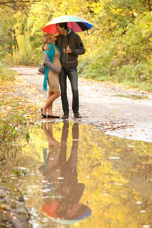 Happy pregnant woman and a man walking in the autumn forest under a rainbow colorful umbrella and reflected in a puddle Stock Photo - 15812537
